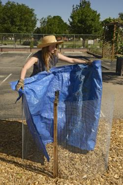 Young woman lining inside of bin with blue tarp