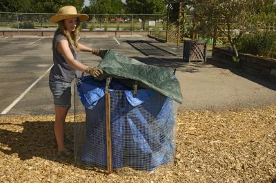 Young woman covering top of bin with plastic tarp